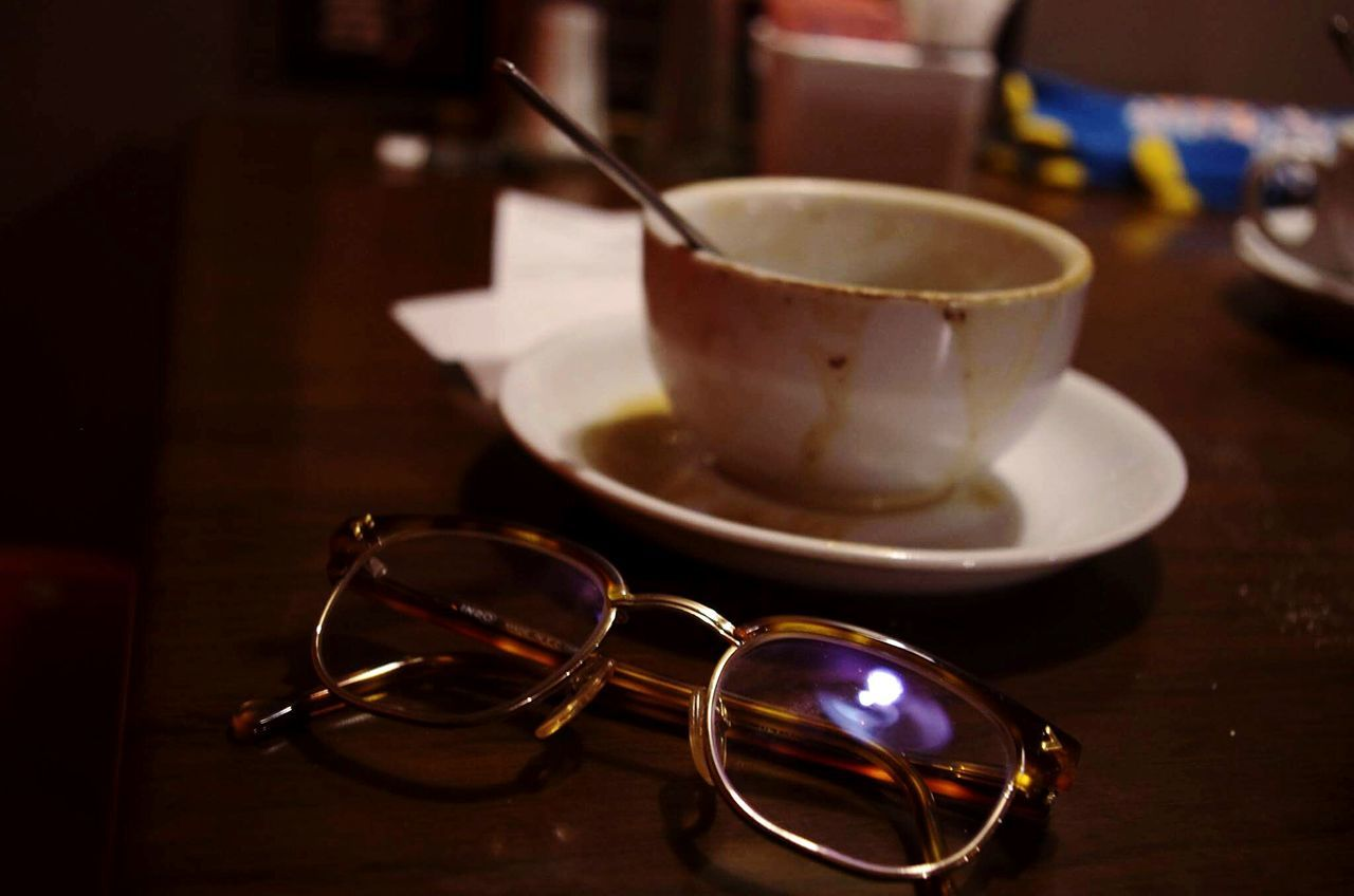 Close-Up Of Eyeglasses And Cup With Saucer On Table