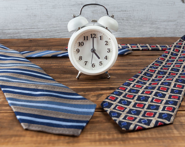 Nine to five working hours business concept with vintage alarm clock and ties Business Nine To Five Alarm Clock Business Finance And Industry Clock Close-up Concept Conceptual Corporate Day Fathers Day Hardwood Floor High Angle View Indoors  No People Table Technology Tie Time Wood - Material