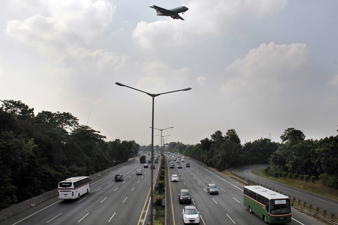 Airplane Flying Over Vehicles On Roads