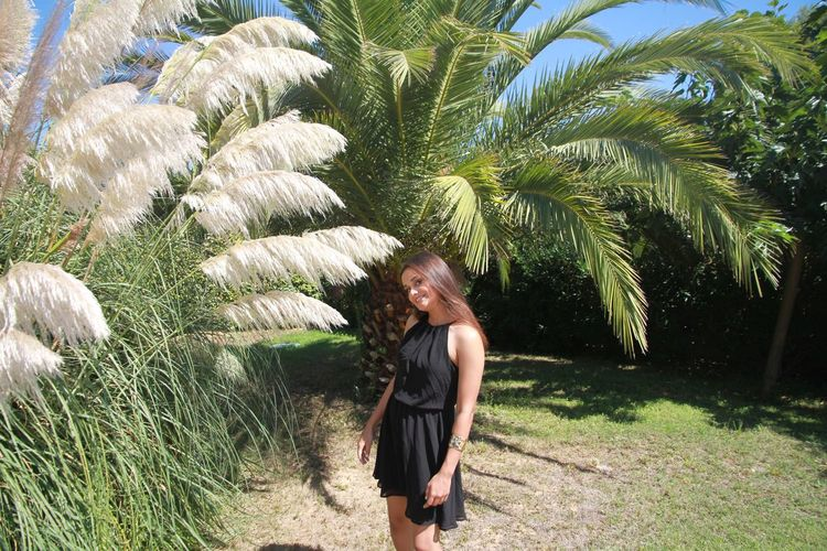 Palm Tree One Person Real People Young Women Young Adult Standing Leisure Activity Smiling Nature Day Plant Outdoors Lifestyles Beautiful Woman Tree Grass One Young Woman Only Adults Only Adult