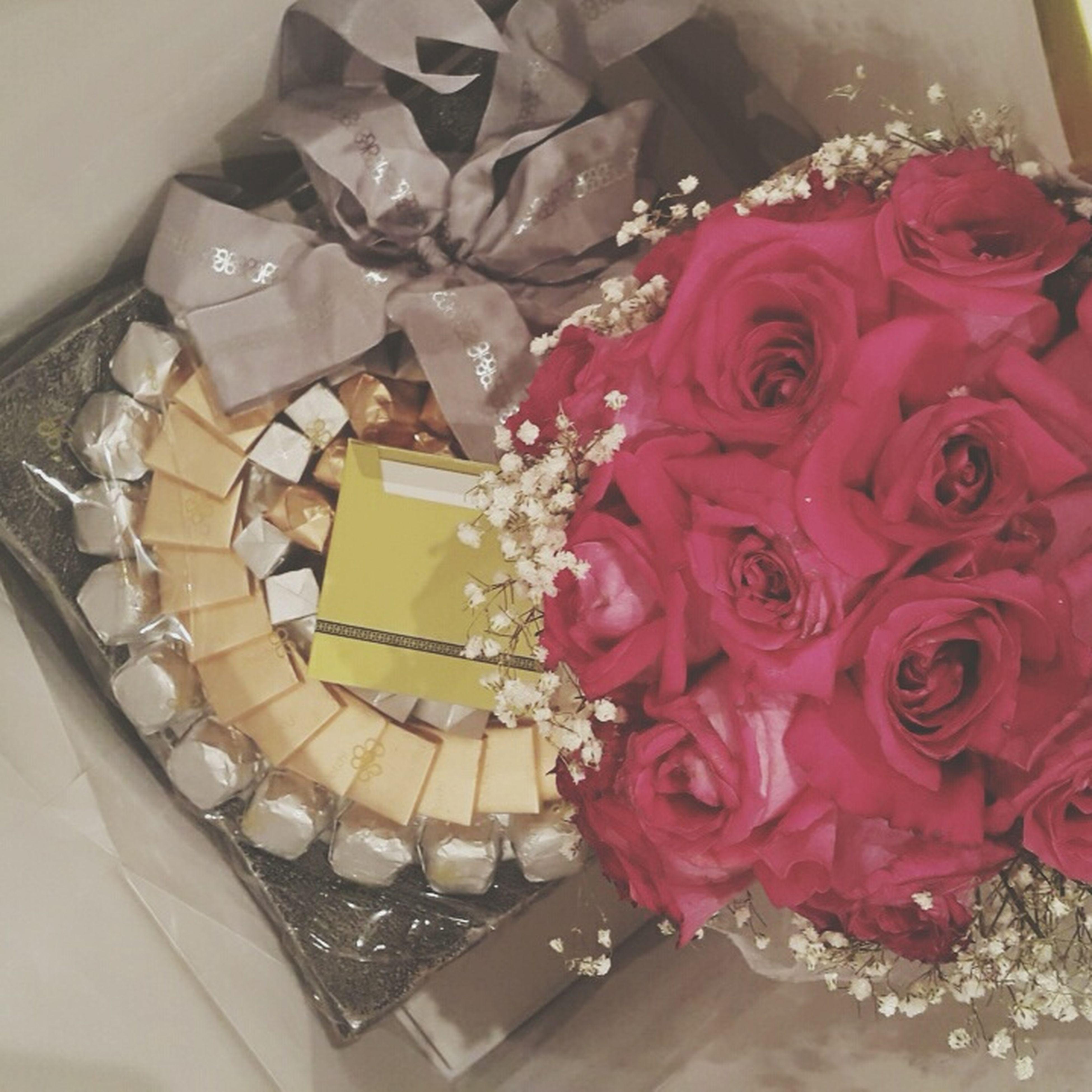 indoors, flower, still life, decoration, close-up, table, rose - flower, freshness, high angle view, pink color, sweet food, home interior, celebration, vase, red, no people, dessert, bouquet, cake, petal