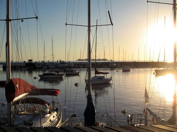 The sun going down behind the Yachting Club at Colonia del Sacramento, Uruguay. Beauty In Nature Holidays Isla San Gabriel Mode Of Transport Moored Nature Nautical Vessel Outdoors Peaceful Evening River Plate Sailing Sails Sea Sky Sun Going Down Sunset Tourist Destination Transportation Water Yacht