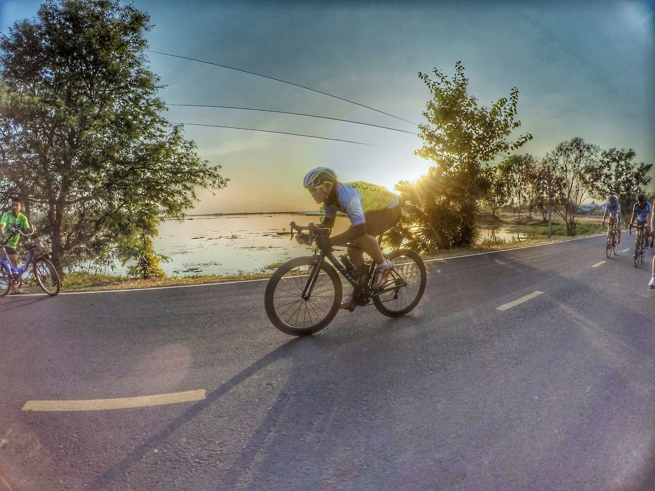road, tree, transportation, bicycle, full length, riding, real people, cycling, two people, men, land vehicle, outdoors, day, cycling helmet, helmet, adventure, sky, friendship, people