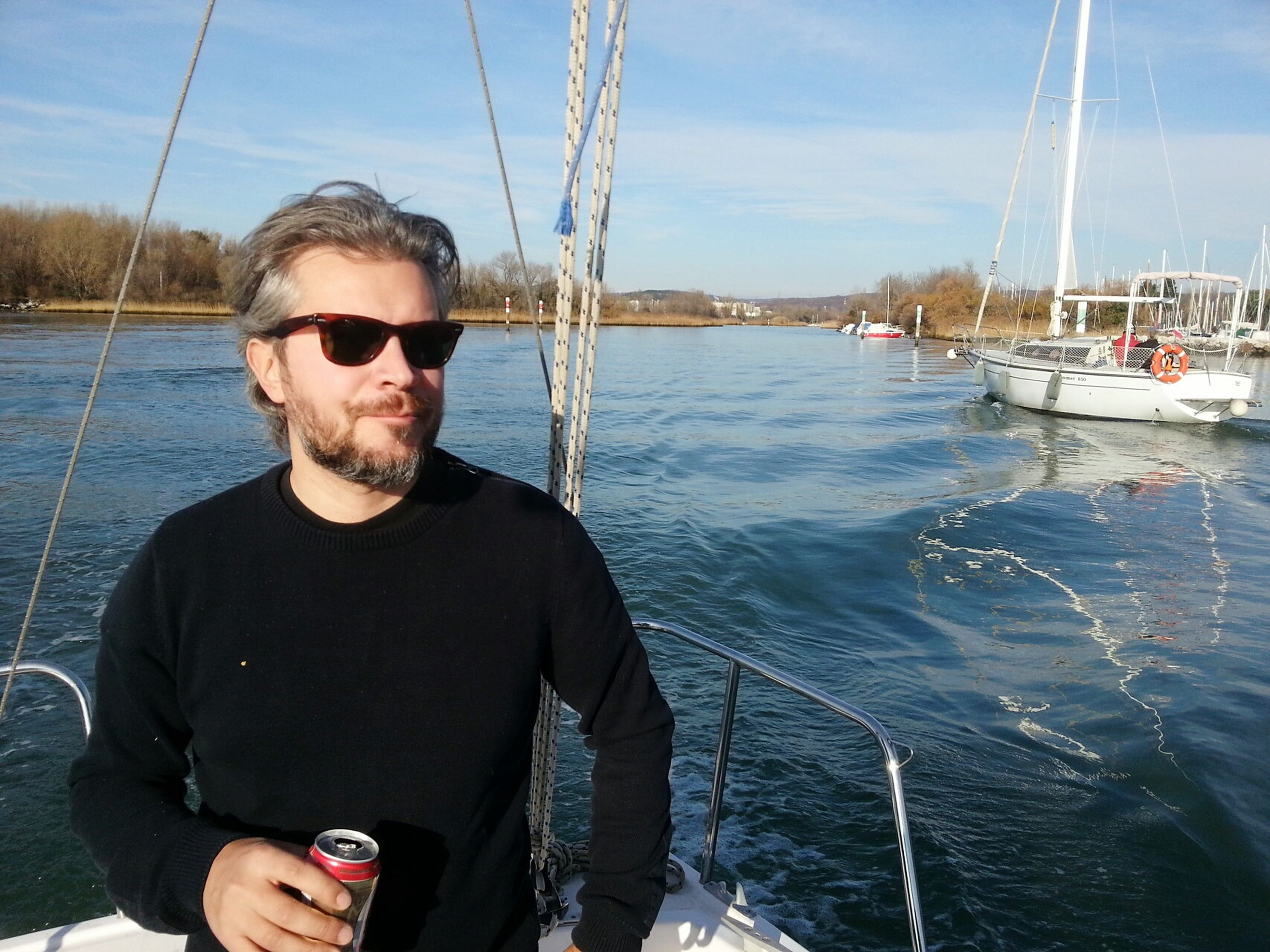 water, lifestyles, leisure activity, person, looking at camera, nautical vessel, transportation, portrait, young adult, mode of transport, casual clothing, young men, sky, front view, sunglasses, boat, smiling, day
