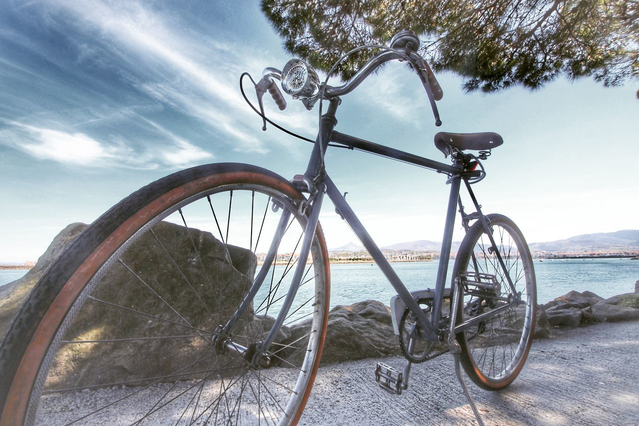 transportation, bicycle, mode of transport, land vehicle, stationary, wheel, day, sky, outdoors, no people, cloud - sky, sea, spoke, nature, water, tree, childhood