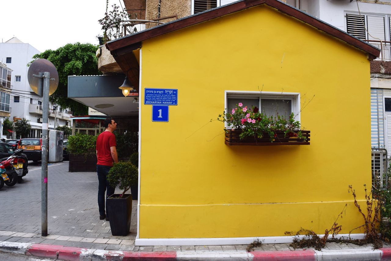 City Life in Tel Aviv Israel Building Exterior Architecture Built Structure Yellow Outdoors Summer Yellow Background Yellow Color Colorful City Street Yellow House  House One Person Real People Residential Building Full Length Standing City Adult People Neon Life Plant Nursery