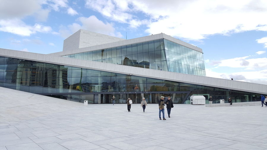 The Oslo Opera House (Norwegian: Operahuset) is the home of The Norwegian National Opera and Ballet, and the national opera theatre in Norway. The building is situated in the Bjørvika neighborhood of central Oslo, at the head of the Oslofjord. It is operated by Statsbygg, the government agency which manages property for the Norwegian government. The structure contains 1,100 rooms in a total area of 38,500 m2 (414,000 sq ft). The main auditorium seats 1,364 and two other performance spaces can seat 200 and 400. The main stage is 16 m (52 ft) wide and 40 m (130 ft) deep. The angled exterior surfaces of the building are covered with Italian marble and white granite and make it appear to rise from the water. It is the largest cultural building constructed in Norway since Nidarosdomen was completed circa 1300. Architectural Detail Architecture Architecture_collection Architecturelovers Ballet Ballett Contemporary Contemporary Art EyeEm Best Shots Granite Hidden Gems  Iceberg Marble Modern Architecture Norwegian Opera House Operaen  Operahouse Operahuset Opéra Oslo Opera House Oslo Operahuset Scandinavia The Purist (no Edit, No Filter) White