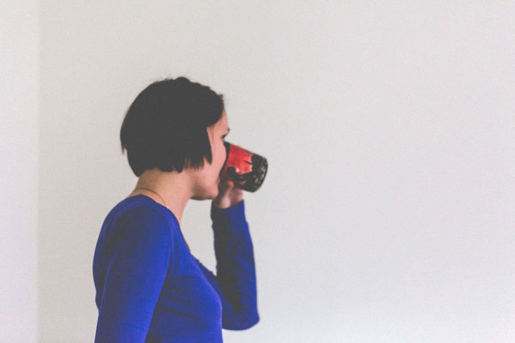 Jung women's drinking a tea on light wall background Adult Adults Only Blue Top Break Cup Drinking Female Girl In-house Indoors  Leisure Activity Lifestyles Light Background Natural Not Posed One Person Short Hair Single Stand Up Tea Time Text Space Enjoy The New Normal Enjoy The New Narmal Always Be Cozy