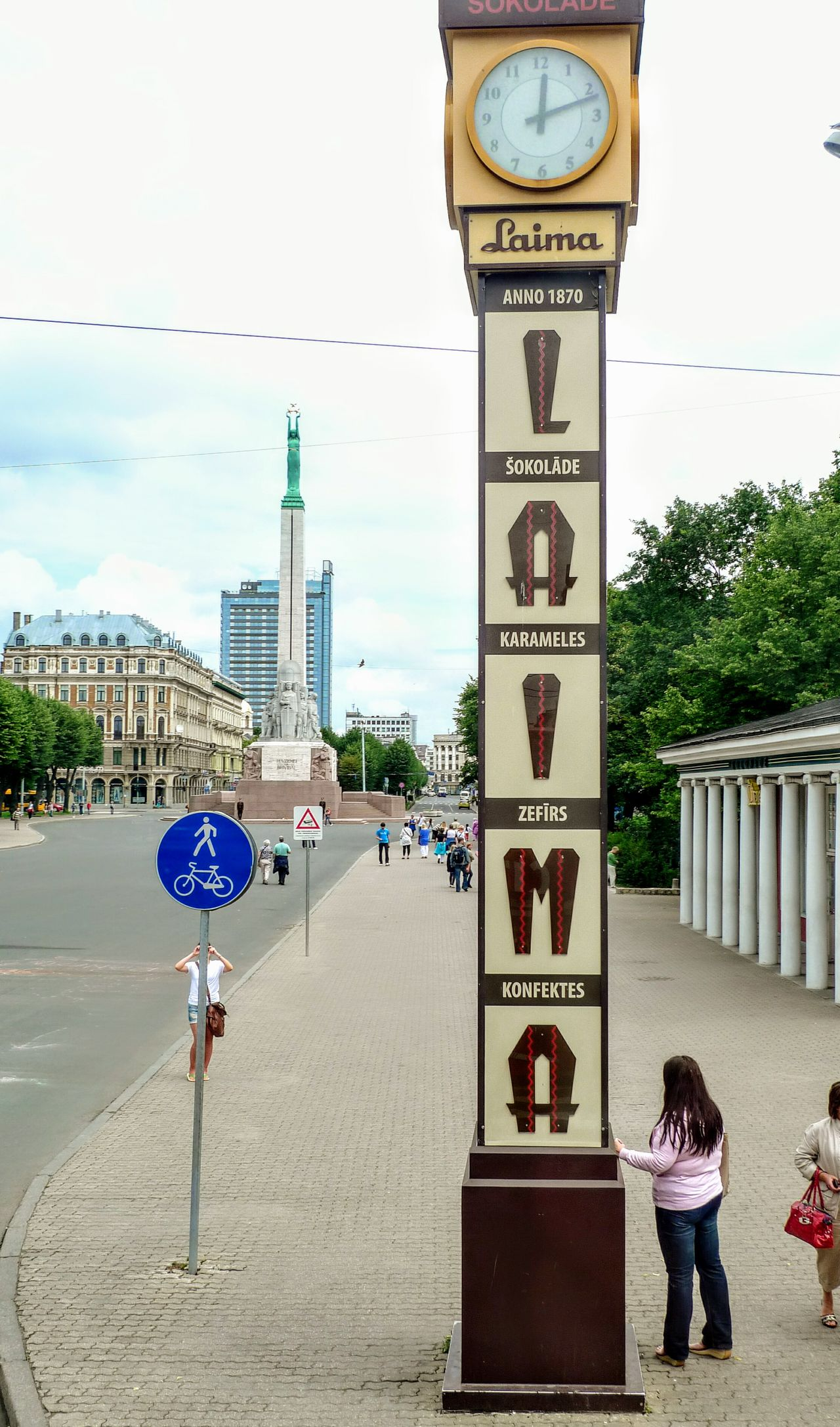 Historic clocktower in Riga, Latvia. Baltic countries Outdoors People Road Sign Sky Adult Baltic Countries Clock Riga City Street Baltic Countries Latvia Latvia Riga City Urban Monument Advertisments Laima Sweets 1924 liberty monument Liberty Monument