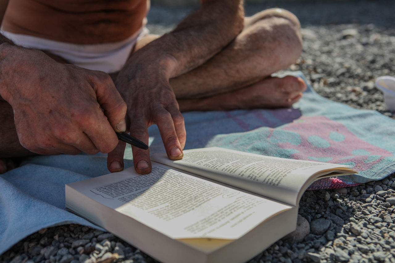 Read a Book on a beach Beach Book Close-up Day Human Body Part Human Hand Indoors  Lifestyles Men One Person People Read Reading Reading A Book Real People Summer Sunny