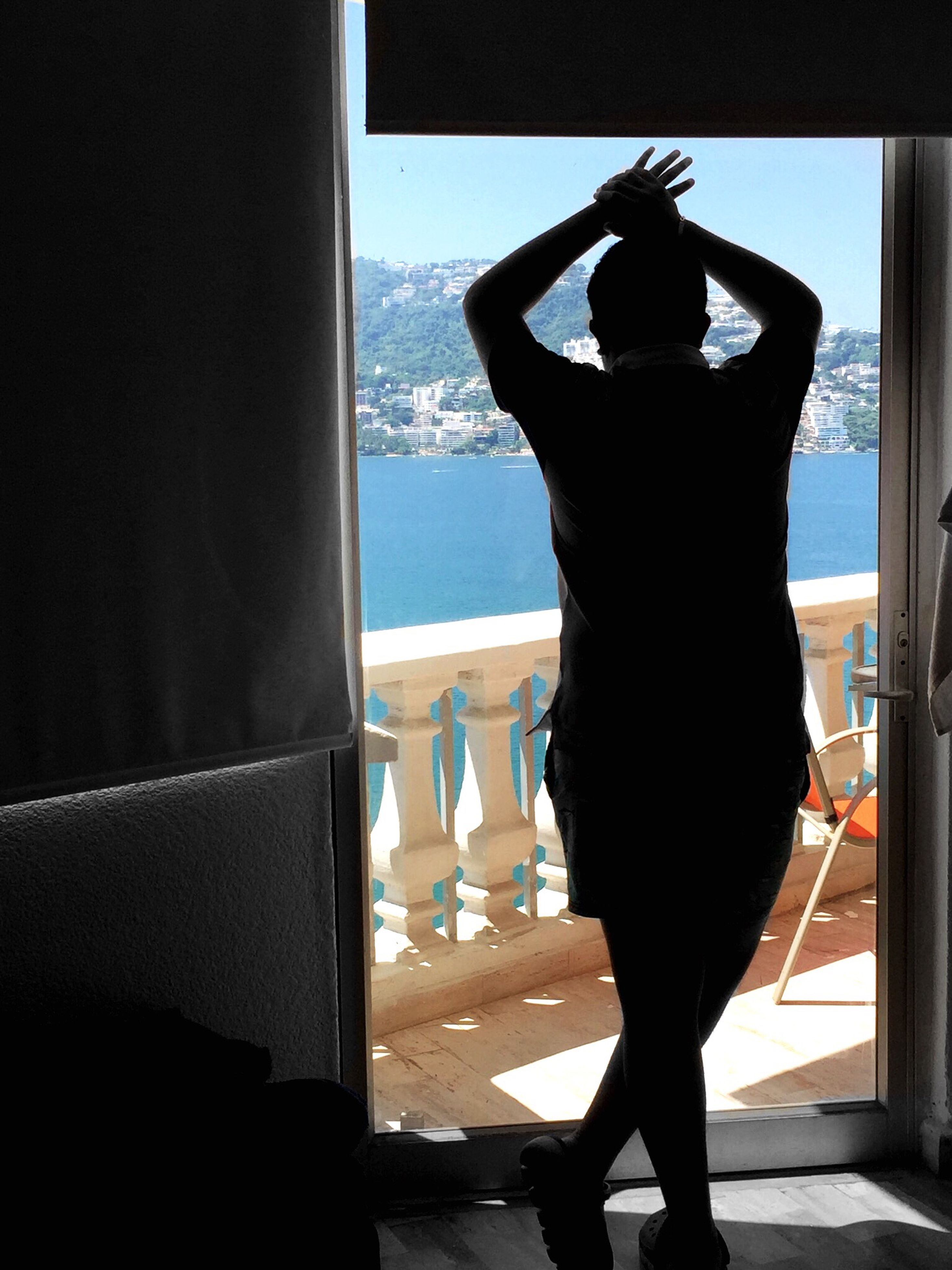 indoors, window, standing, rear view, glass - material, silhouette, looking through window, transparent, full length, sea, home interior, in front of, water, mountain, curiosity, day, nature, domestic life, drapes