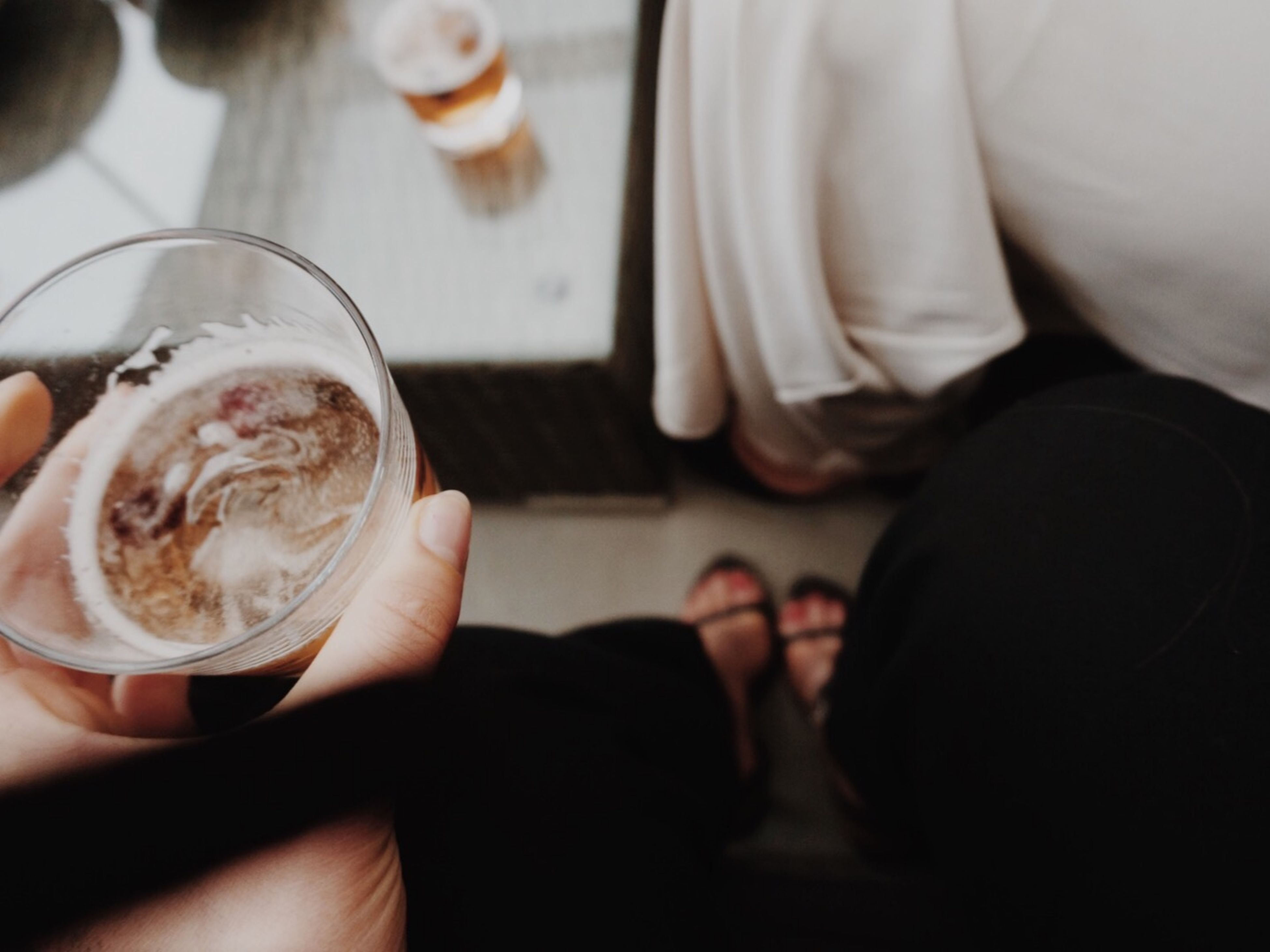 food and drink, drink, indoors, refreshment, freshness, lifestyles, person, coffee - drink, coffee cup, leisure activity, table, holding, men, close-up, drinking glass, part of