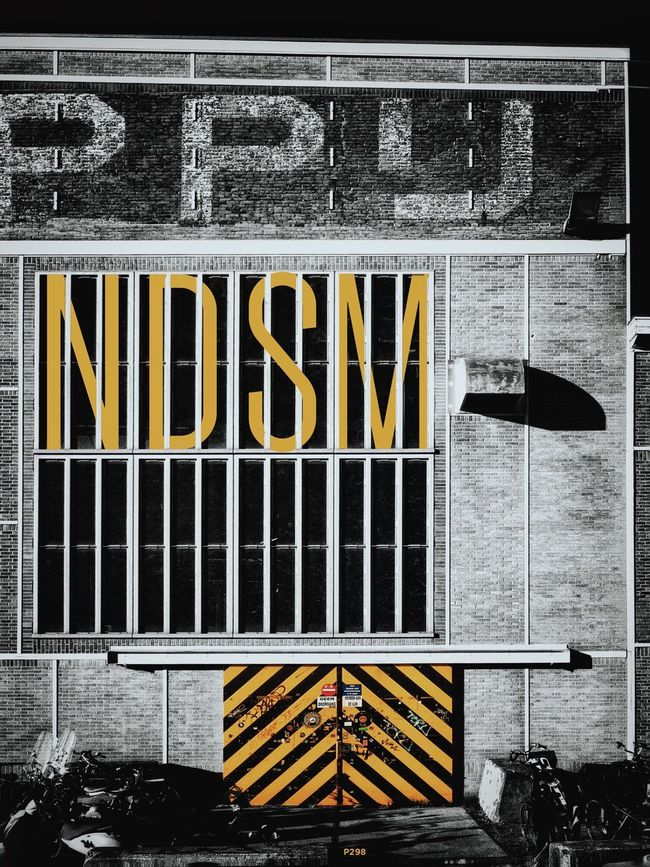 NDSM. P298 Just some layers and type and more layers. Onephotoaday IPhoneography Multiple Layers Blackandwhite Black And White Black & White Black And Yellow  Typography Architecture Architectural Detail Historical Building High Contrast Sliding Door Beware IPhone Editing EyeEm Best Edits Bestofover Outdoors Nopeople Streetphotography