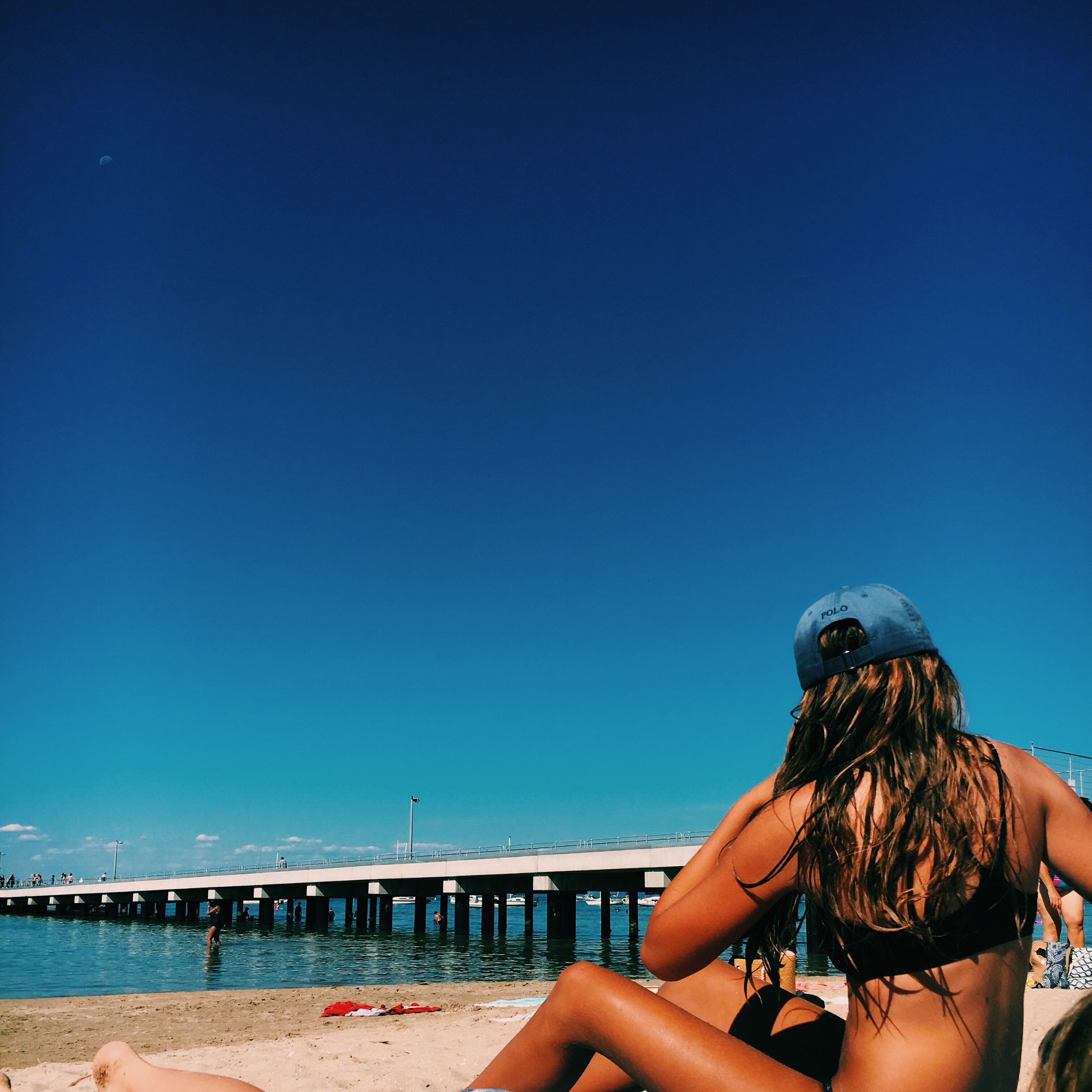 clear sky, blue, sea, copy space, water, lifestyles, leisure activity, beach, rear view, person, relaxation, young adult, vacations, horizon over water, sitting, shore, casual clothing, sunlight