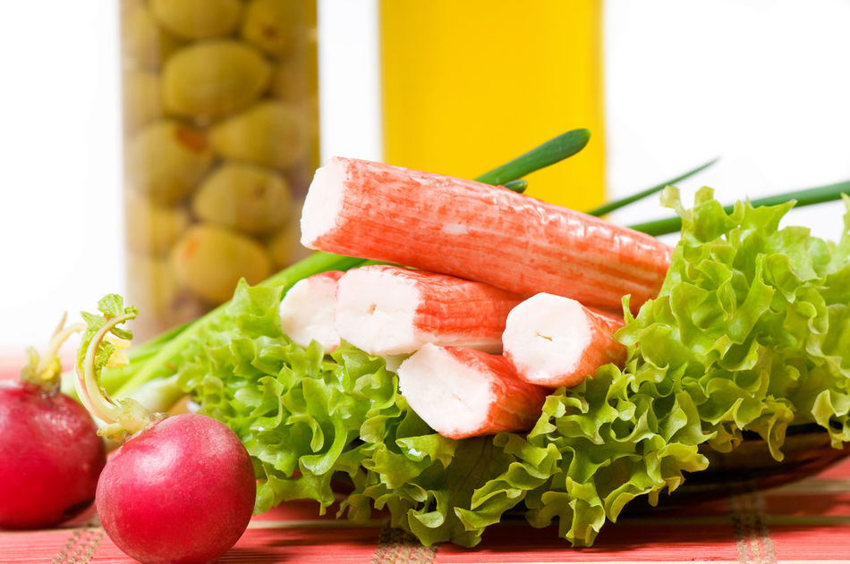 Crab sticks of surimi imitation on lettuce leaf with red radish and olives with oil in glass jar behind, objects in horizontal orientation, nobody. Crab Food Food And Drink Freshness Lettuce No People Olives Radish Ready-to-eat Red Stick Sticks Surimi
