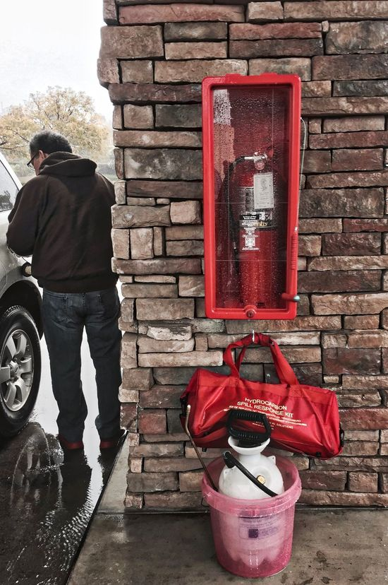 Adult Adults Only Brick Wall Day Emergency Fire Extinguisher Gas Station Gasoline Getting Gas Men One Man Only One Person Only Men Outdoors People Precautions Preparation  Red Safety