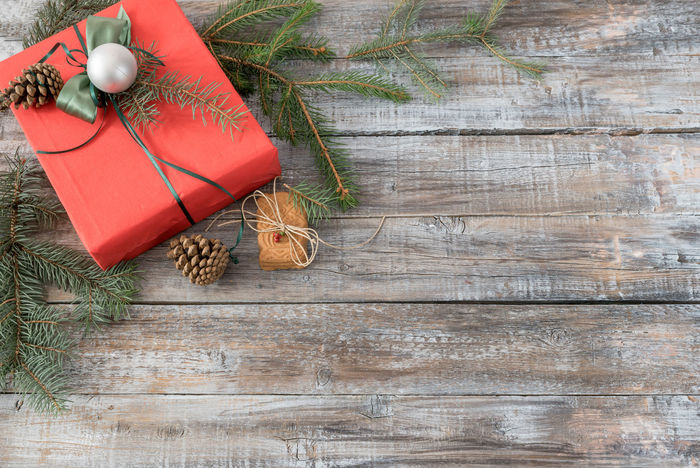 Xmas or New Year background holiday plain composition made of Christmas decorations on a wooden background, top view with copy space Branch Christmas Christmas Decoration Christmas Ornament Christmas Present Christmas Tree Day High Angle View Indoors  No People Red Ribbon - Sewing Item Sphere Table Tradition Wood - Material