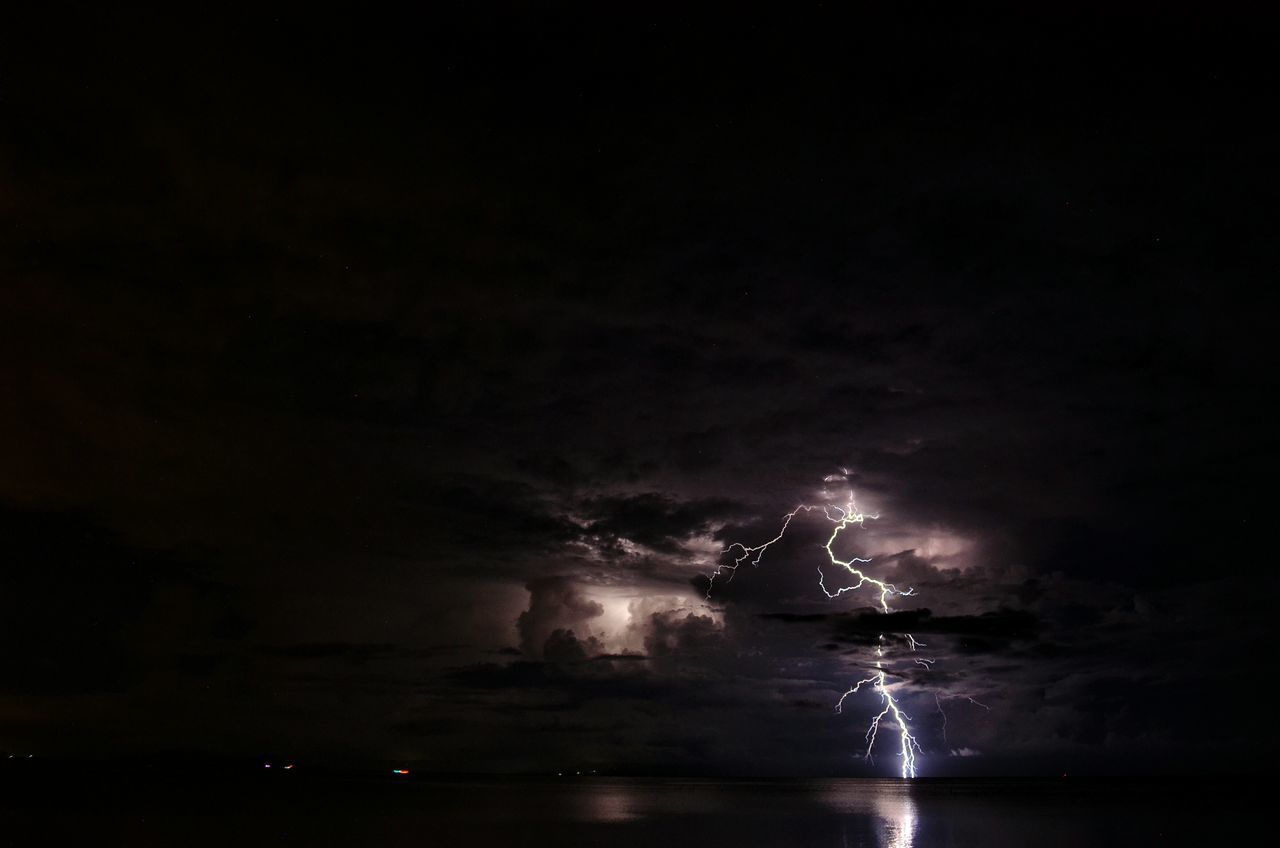 Lightning at night. Lightning Outdoors Thunderstorm Night Power In Nature Sea And Sky Beachatnight Lightning Strikes Sky Nature