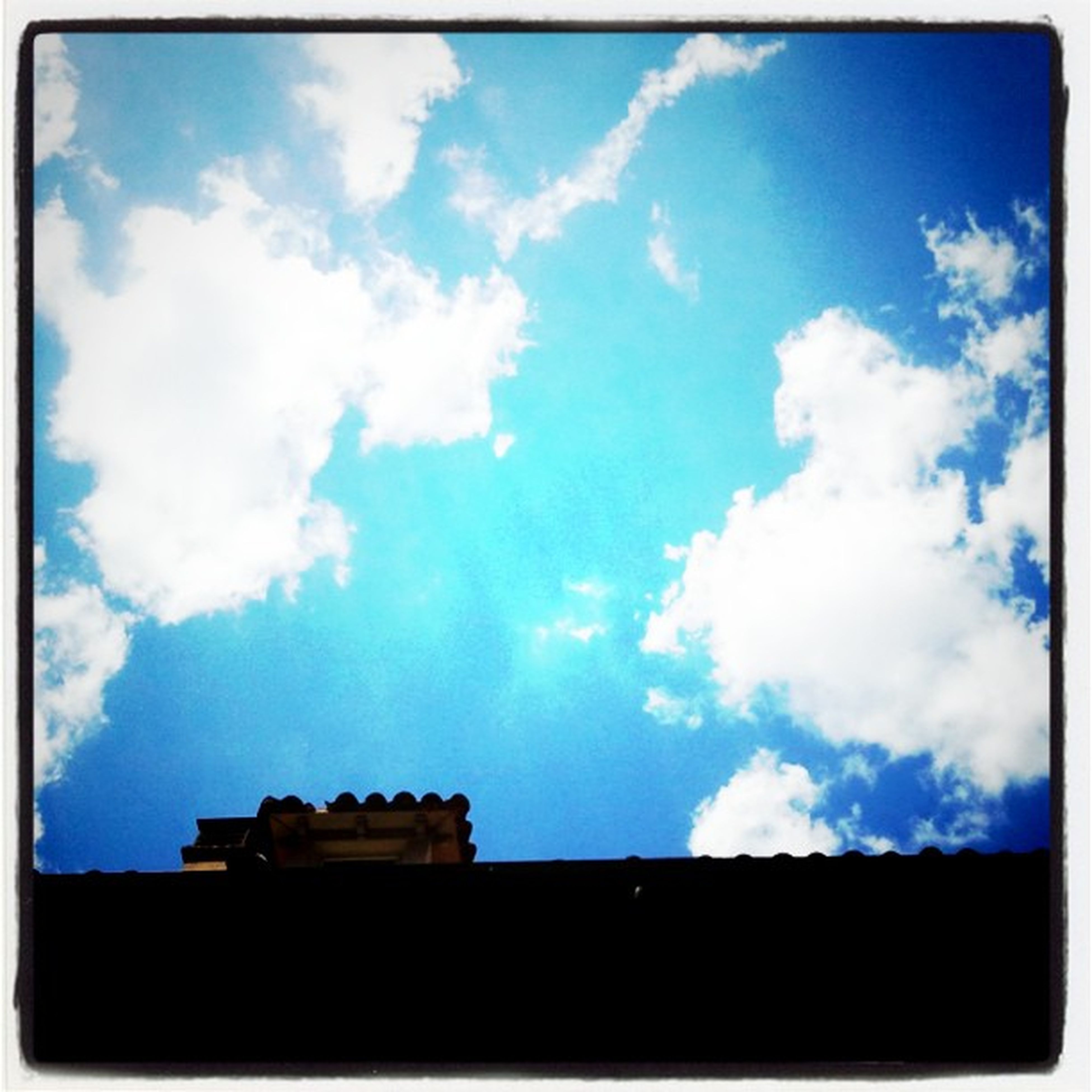 low angle view, sky, transfer print, building exterior, built structure, architecture, blue, cloud - sky, auto post production filter, silhouette, cloud, high section, outdoors, house, cloudy, no people, building, day, nature, sunlight
