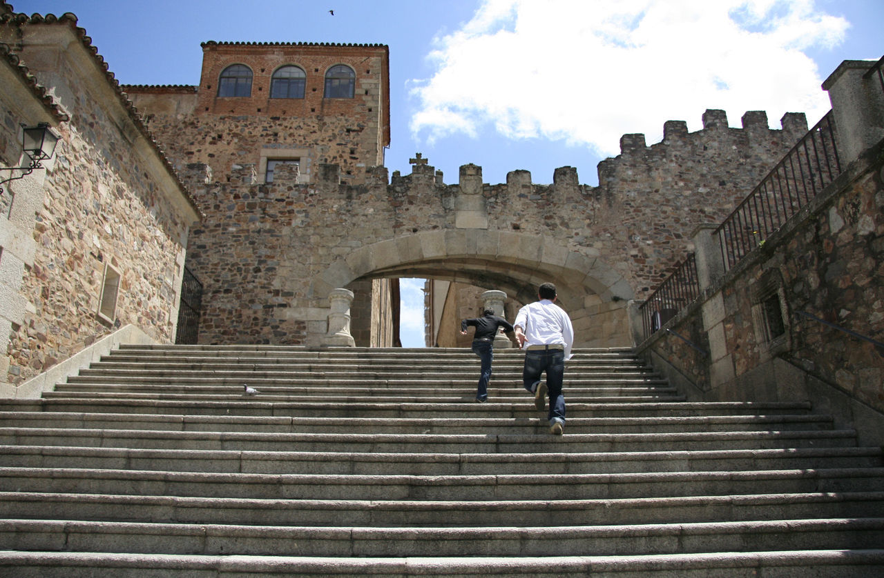 Two guys running up the Estrella Arch stairs, at Caceres Old Town Adult Adults Only Architecture Building Exterior City Cloud - Sky Day Full Length History Low Angle View Medieval Men One Man Only One Person Only Men Outdoors People Real People Sky Staircase Steps Steps And Staircases Travel Destinations