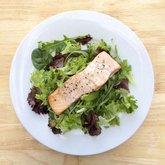 Salmon steak on a bed of mixed salad leaves Black Pepper Close Up Close-up Detail Directly Above Fish Food Food And Drink Freshness Green Color Healthy Eating High Angle View Leaf Salad Leaves Lunch Meal No People Plate Ready-to-eat Salmon Seasoned Serving Size Steak Table White