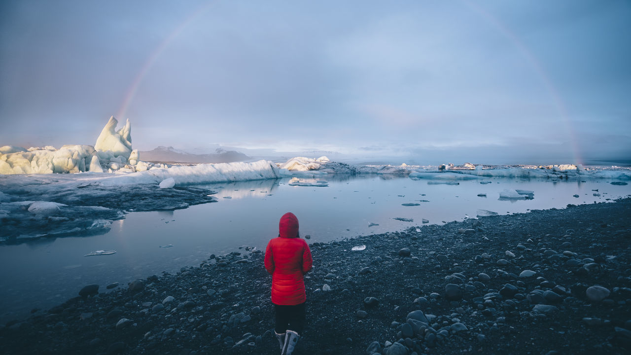 Back View Beauty In Nature Cold Temperature Glacier Glacier Lagoon Iceberg Iceland Jökulsárlón Glaciar Lagoon Nature One Person Outdoors Rainbow Rainbows Red Scenics Tranquil Scene Tranquility Walking Water Winter The Great Outdoors - 2017 EyeEm Awards Let's Go. Together.