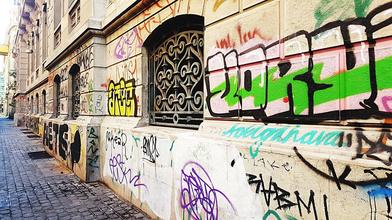 graffiti, text, street art, outdoors, day, multi colored, communication, built structure, architecture, no people, building exterior, city, painted image
