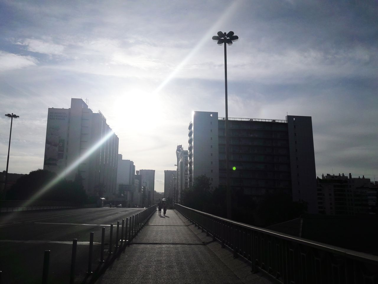 architecture, built structure, skyscraper, city, sky, cloud - sky, sunlight, the way forward, outdoors, building exterior, real people, day, modern, cityscape, one person, people
