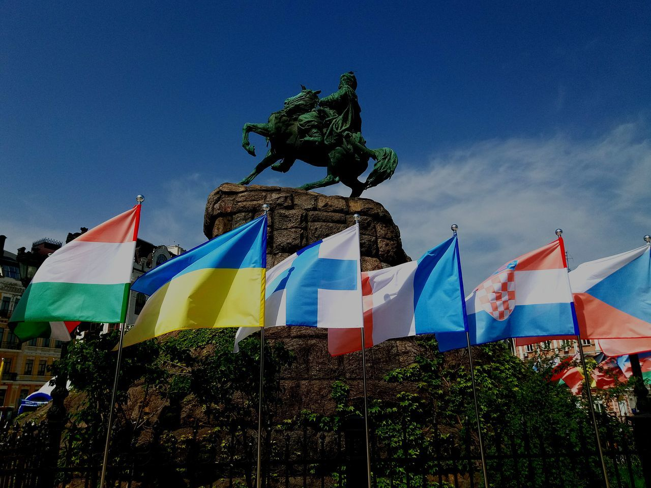 flag, patriotism, blue, statue, outdoors, sky, multi colored, pride, day, low angle view, clear sky, no people, sculpture, tree, architecture