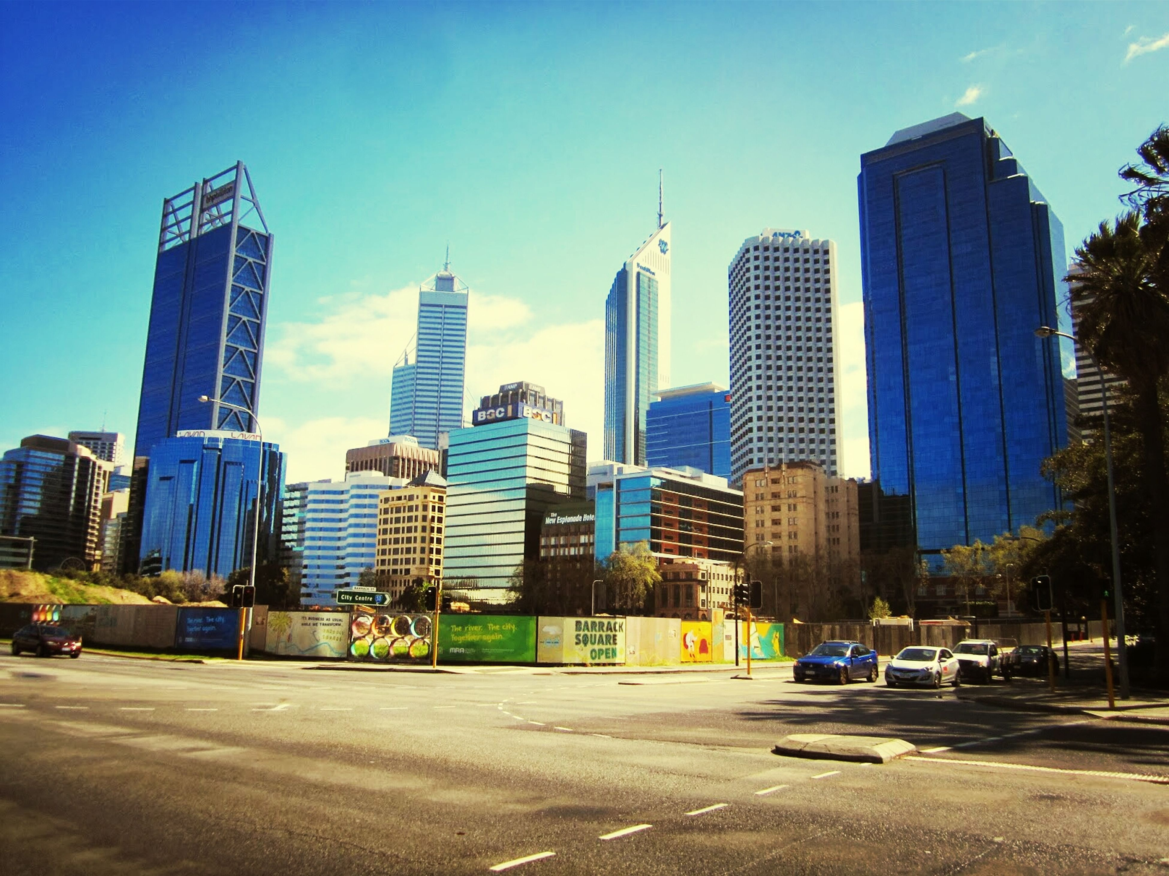 building exterior, architecture, city, built structure, skyscraper, office building, modern, tall - high, tower, blue, street, road, cityscape, urban skyline, building, city life, sky, car, financial district, transportation