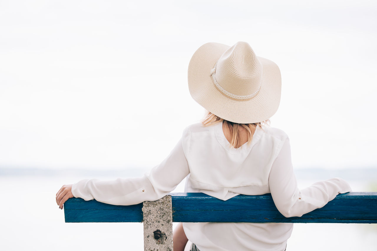hat, real people, one person, sun hat, lifestyles, rear view, leisure activity, women, relaxation, sea, sitting, outdoors, young adult, young women, beauty in nature, day, water, nature, sky