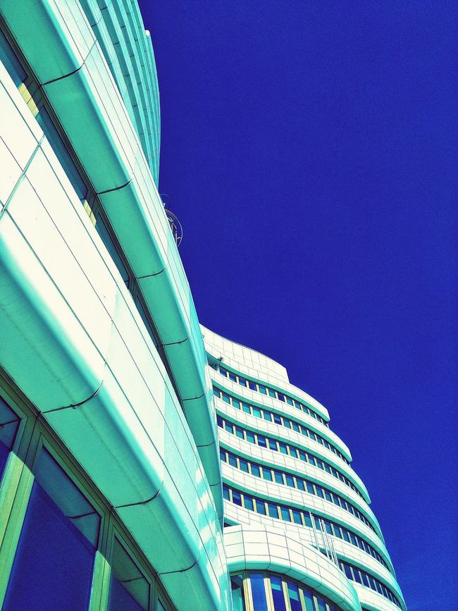 Low Angle View Architecture Built Structure Clear Sky Building Exterior Blue City Modern High Section Outdoors City Life Day Building Story Tall - High Skyscraper Sky Office Building Development No People Architectural Feature Architecture ModernDiminishing Perspective Geometric Shape