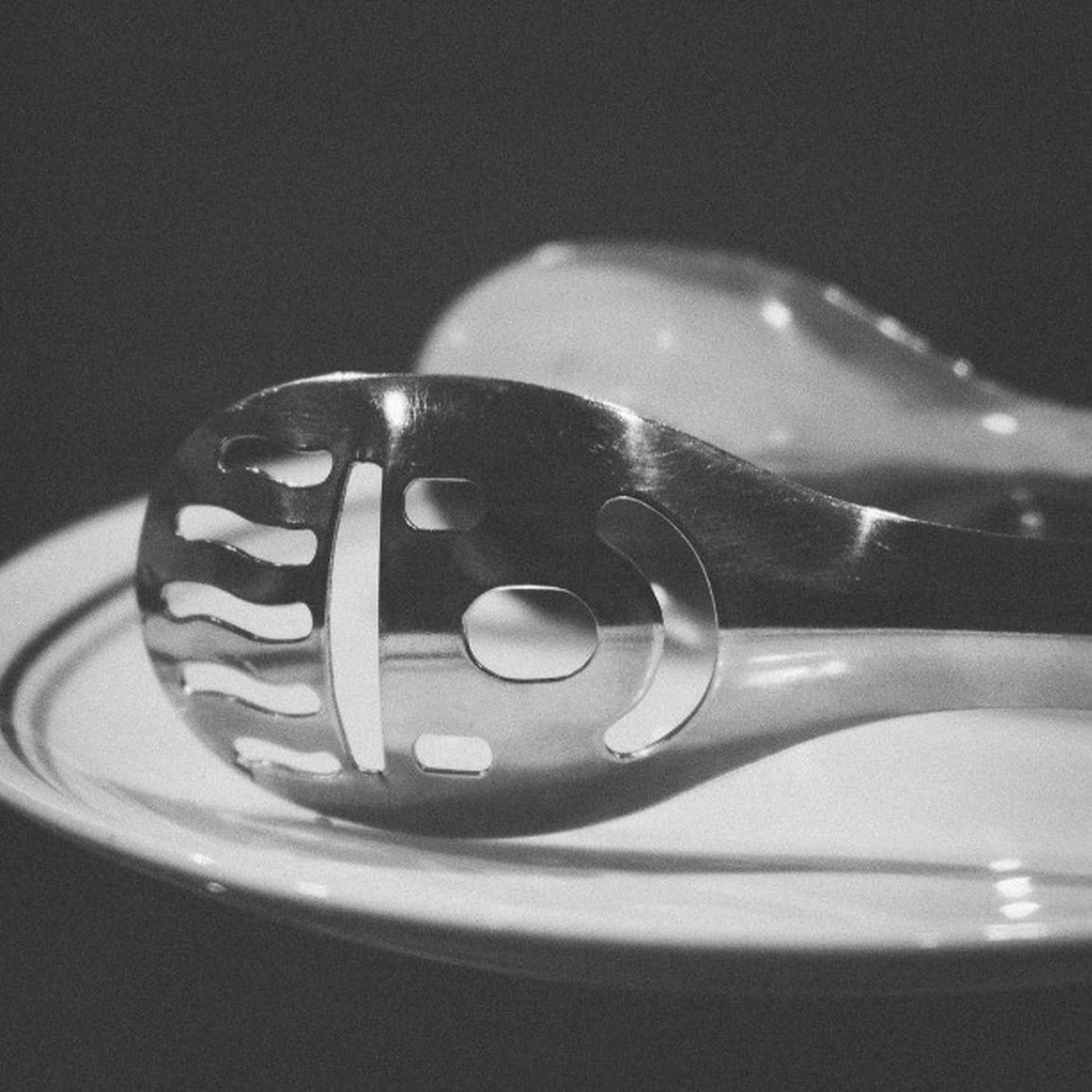 indoors, close-up, still life, table, high angle view, technology, single object, selective focus, no people, focus on foreground, metal, studio shot, black color, shiny, man made object, detail, reflection, old-fashioned, music, sink