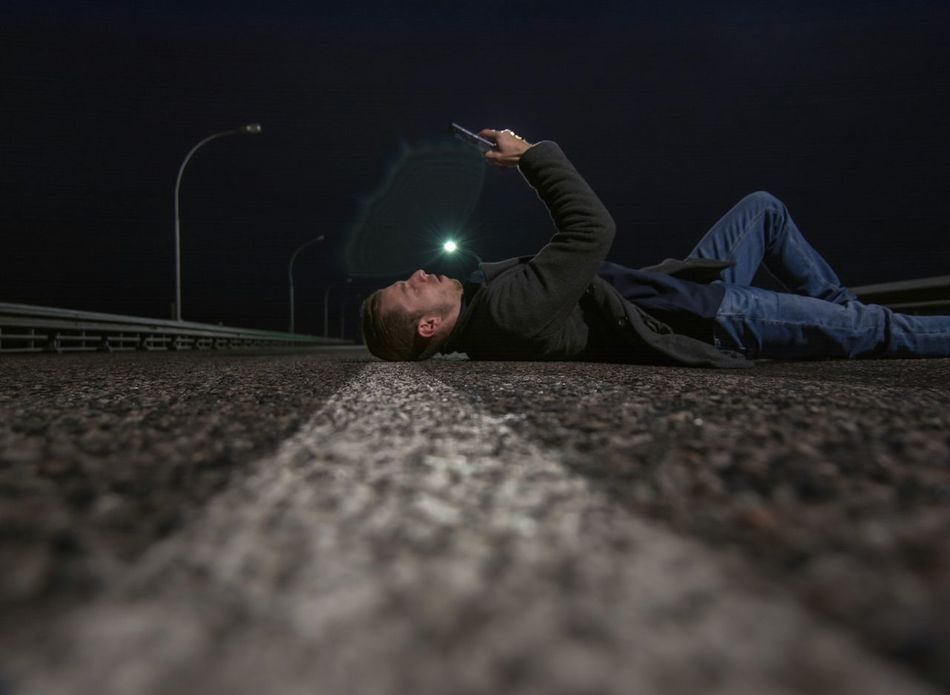 EyeEm Selects Night One Person One Man Only Surface Level Lie Lying Down Road Asphalt Outdoors Young Adult The Week On EyeEm Individuality From My Point Of View By Ivan Maximov Portrait Of Man Lifestyle Illuminated Eyeem Photo One Young Man Only Road Marking Night View Night Road Full Length RISK