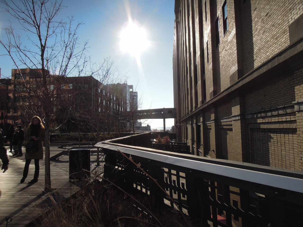 architecture, sunlight, sun, built structure, real people, sunbeam, building exterior, sky, railing, one person, full length, day, outdoors, women, lifestyles, standing, men, tree, city, nature, people