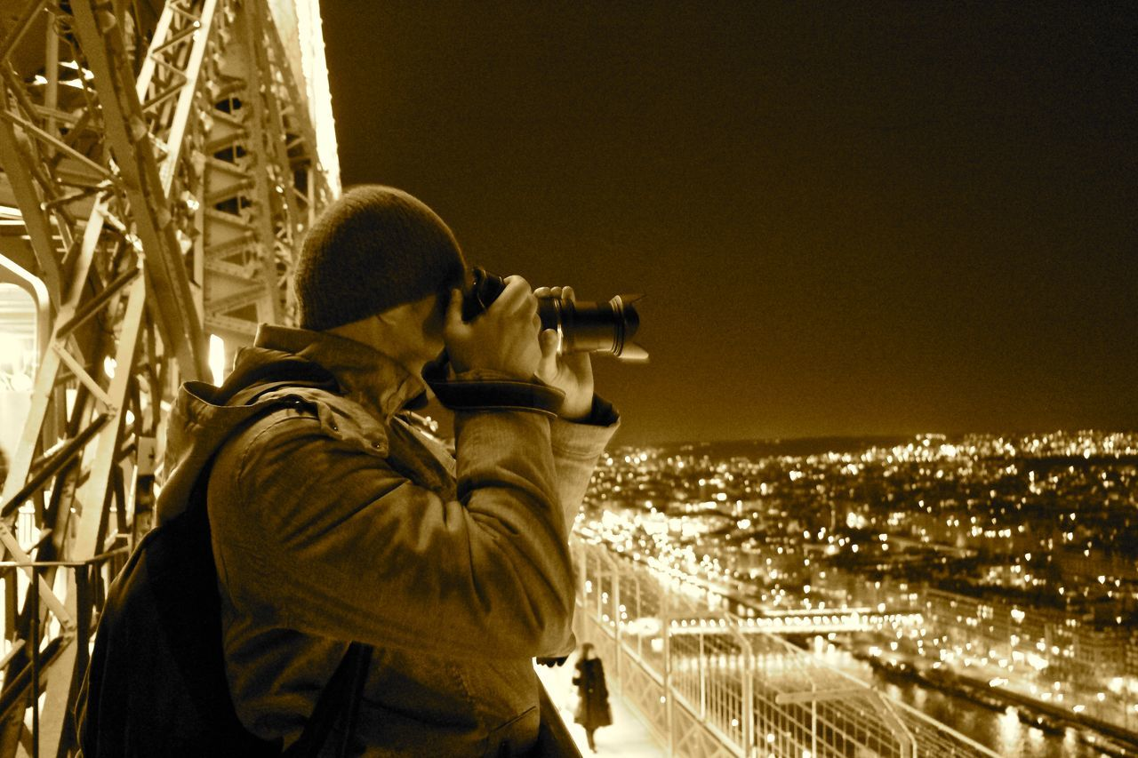 real people, leisure activity, photographing, illuminated, night, lifestyles, photography themes, outdoors, one person, camera - photographic equipment, architecture, men, building exterior, standing, city, nature, clear sky, cityscape, technology, sky, digital single-lens reflex camera, people