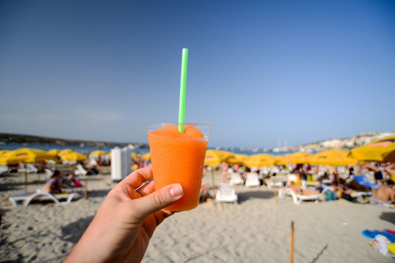 drinking straw, drink, real people, human hand, food and drink, beach, human body part, cocktail, focus on foreground, refreshment, drinking glass, holding, sand, close-up, outdoors, lifestyles, one person, leisure activity, summer, day, women, freshness, clear sky, healthy eating, smoothie, tropical drink, sky, people