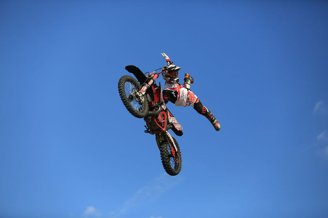 Waving in the skies. Adult Blue Clear Sky Competitive Sport Danger Day Extreme Sports Flying Jumping Low Angle View Men Mid-air Motion Motocross One Person Outdoors People Real People RISK Sky Stunt Stunt Person