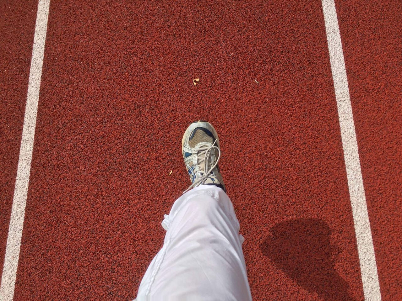 low section, human leg, personal perspective, shoe, high angle view, one person, human body part, red, day, directly above, real people, outdoors, lifestyles, standing, sport, adult, one man only, adults only, people