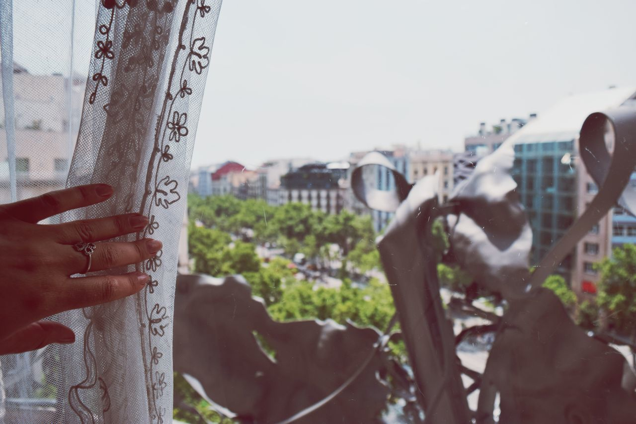 Gaudi View Window View Curtain Human Hand Human Body Part Human Finger Focus On Foreground Communication Lifestyles Outdoors One Person Real People Close-up Sky City Life City Cityscape Tree People Barcelona Romantic Lace Travel Destinations Tourist Attraction
