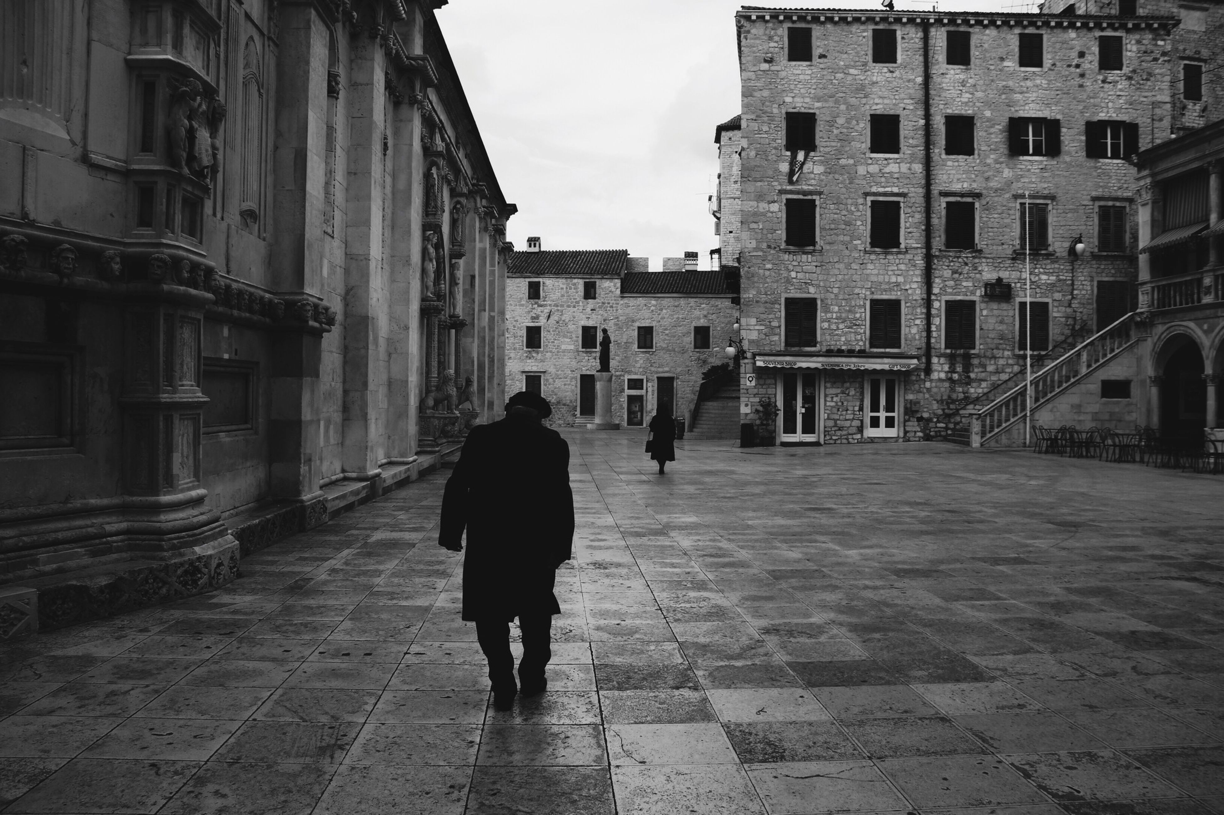 building exterior, architecture, built structure, walking, full length, rear view, street, men, city, lifestyles, the way forward, cobblestone, building, city life, person, residential building, leisure activity, residential structure