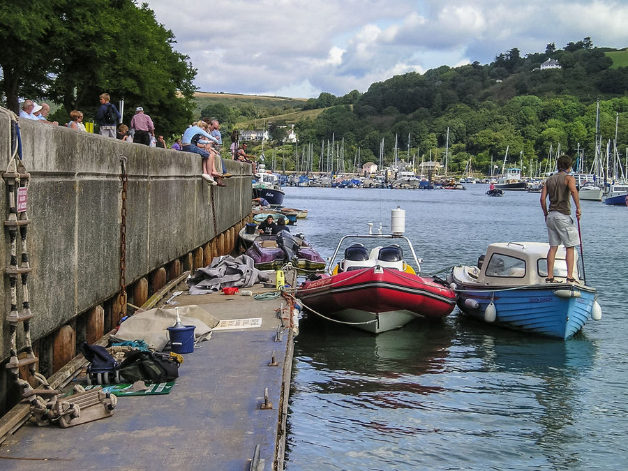 Boats moored against a wall in Dartmouth in South Devon. Boats Cloud - Sky Day Floating Harbour Wall Man Mode Of Transport Moored Moored Boats Nature Nautical Vessel Outdoors People Pontoon Real People River River View Riverscape Sky Transportation Tree Water