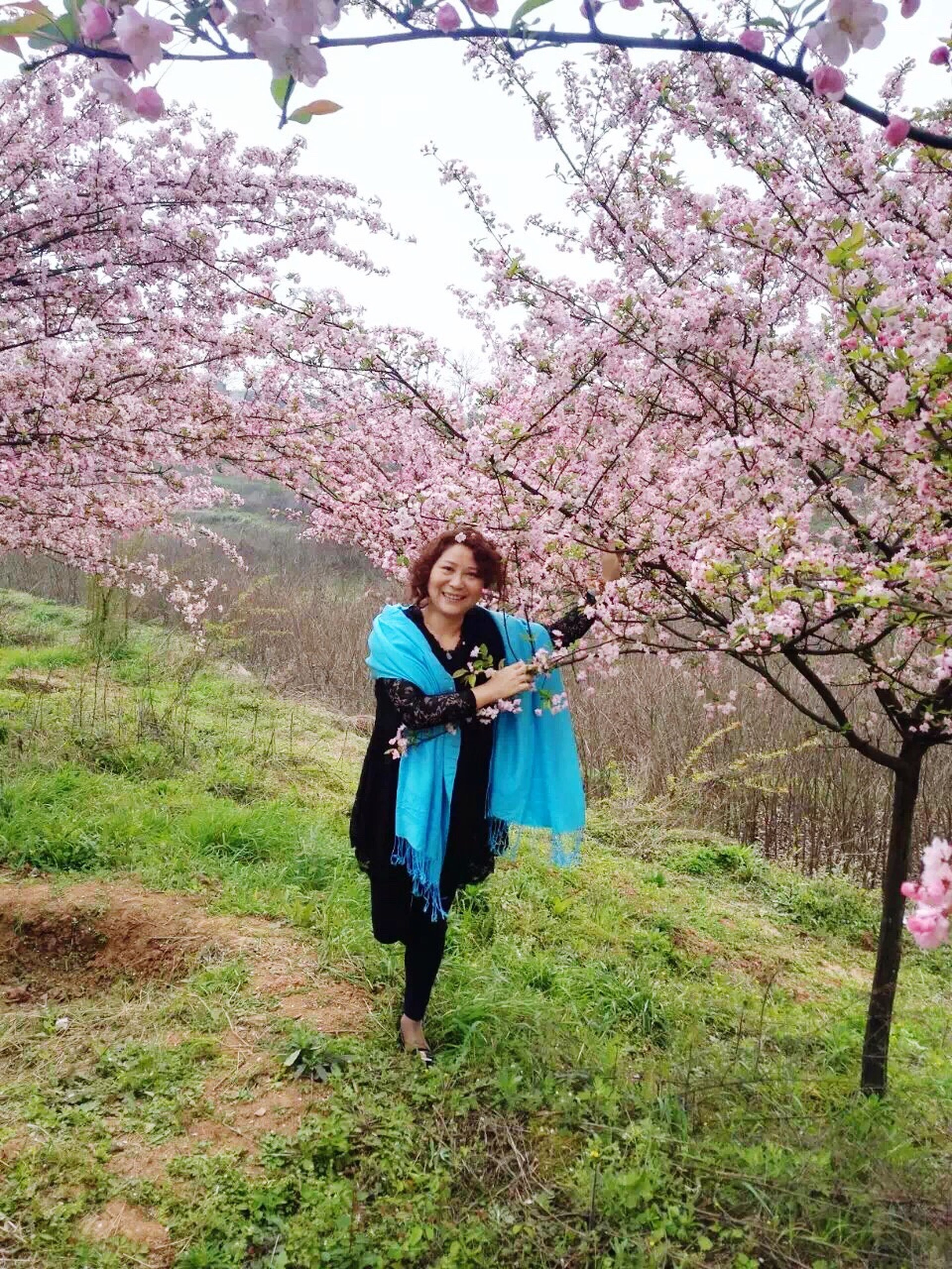lifestyles, casual clothing, leisure activity, person, full length, tree, flower, young adult, looking at camera, standing, nature, young women, smiling, growth, front view, portrait, beauty in nature, childhood