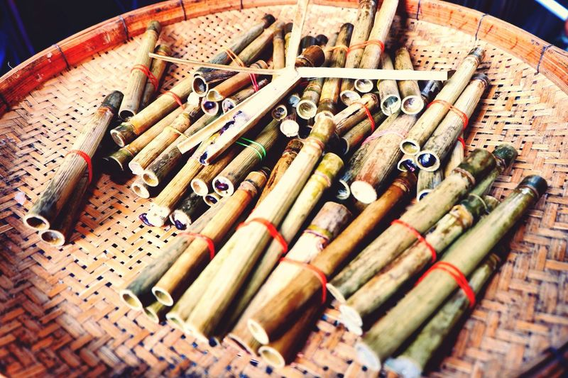 Tiny glutinous rice rosted in bamboo joints on threshing basket Large Group Of Objects No People Abundance Close-up Tiny Glutinous Rice Roasted Bamboo Joints Khao Lam Threshing Basket Sticky Rice Food Coconut Red Bean