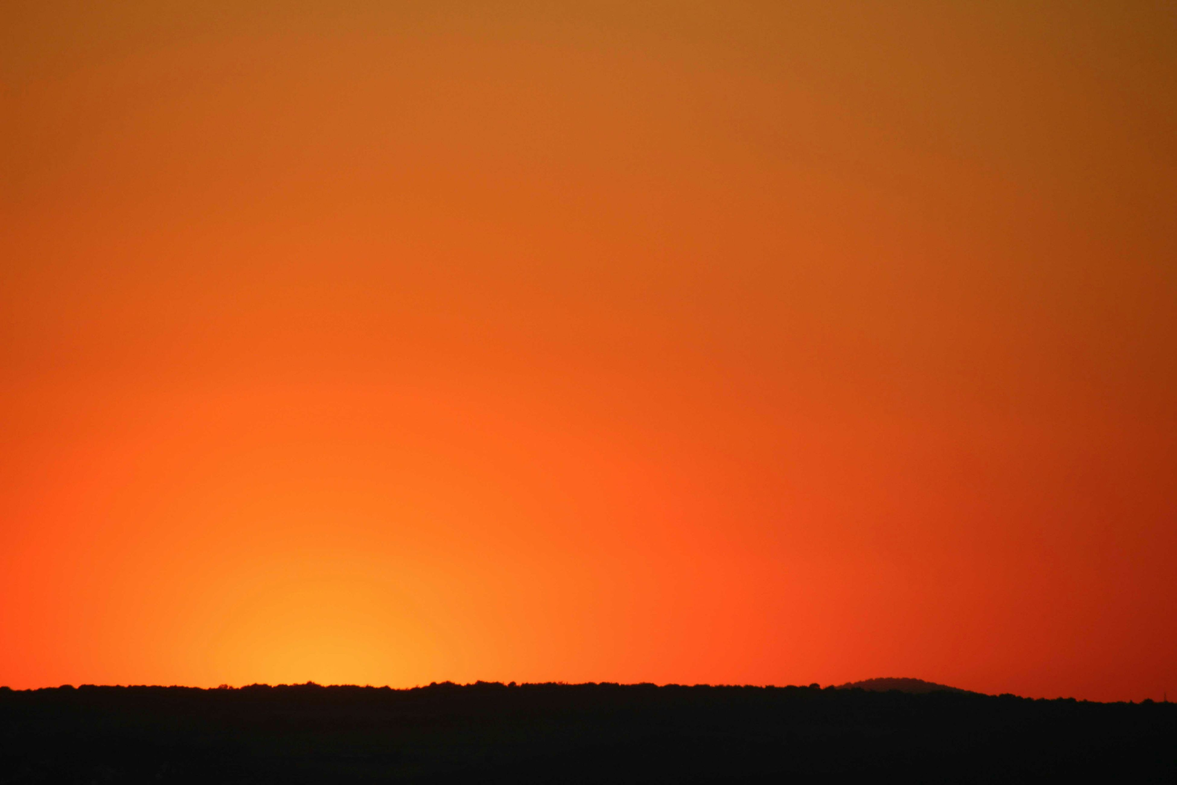sunset, copy space, orange color, silhouette, tranquil scene, clear sky, scenics, tranquility, beauty in nature, landscape, nature, idyllic, dark, horizon over land, outdoors, no people, dusk, remote, majestic, non-urban scene