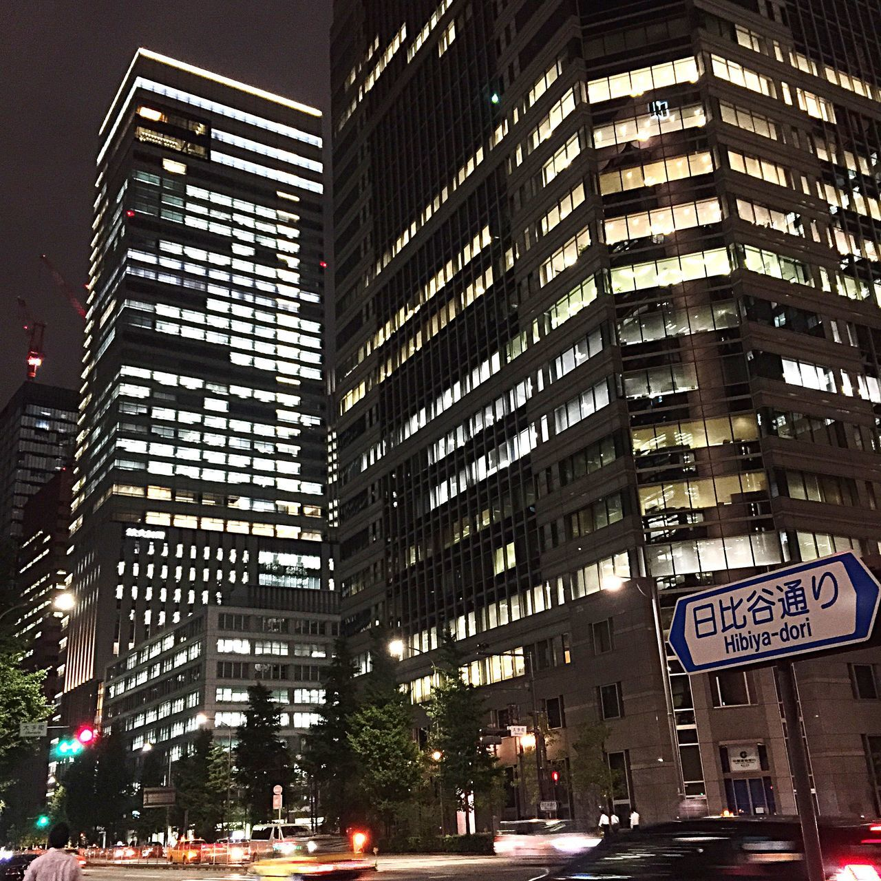 architecture, building exterior, built structure, skyscraper, city, illuminated, night, car, modern, city life, low angle view, outdoors, no people, tree, sky