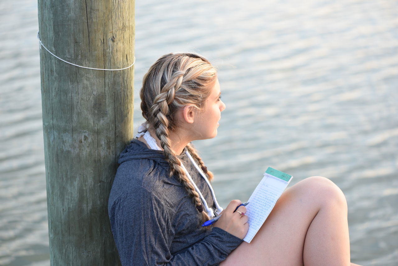 Blond Hair Casual Clothing Contemplation Day Dock Focus On Foreground Lake Leisure Activity Nature One Person Outdoors Real People Side View Sitting Tranquil Scene Water Young Adult Young Women