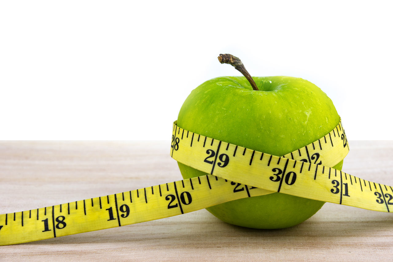 Green apple wrapped with a yellow measuring tape Apple Close-up Diet Food And Drink Fresh Freshness Fruit Green Color Healthy Eating Measuring Tape Obesity Taking Photos Text Vibrant Color Wooden Yellow