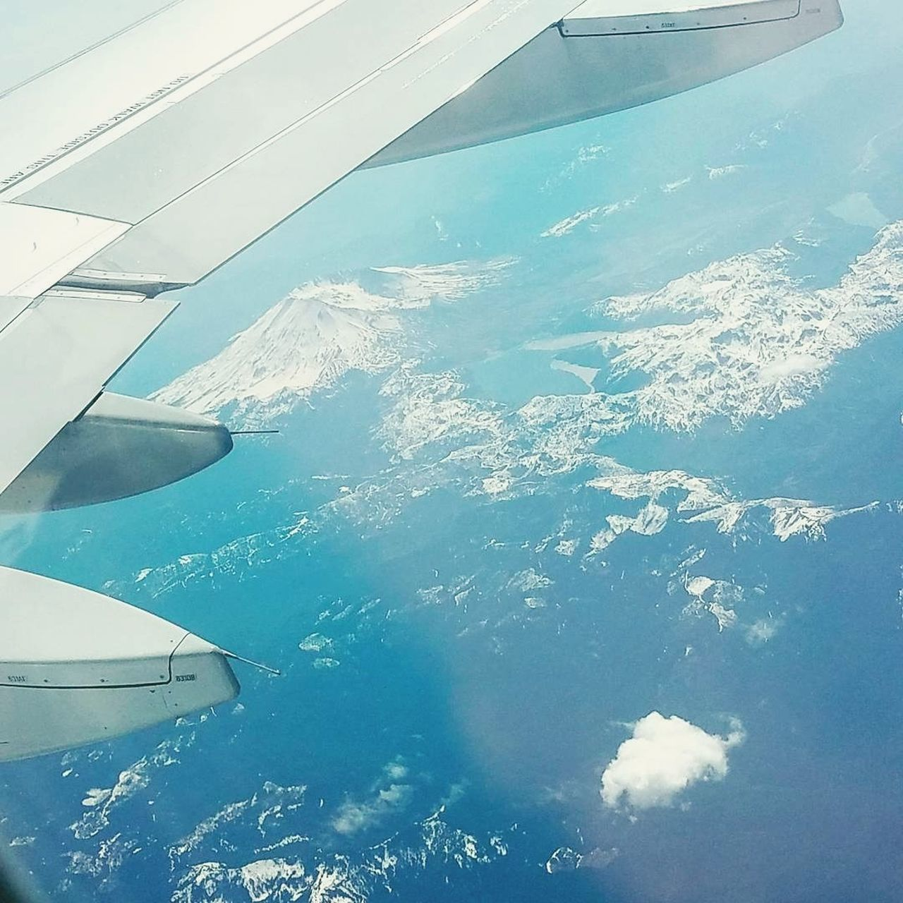 aerial view, airplane, beauty in nature, nature, airplane wing, water, day, no people, travel, journey, scenics, outdoors, air vehicle, tranquil scene, transportation, tranquility, landscape, sky, blue, cold temperature, sea, flying, snow, mountain, view into land