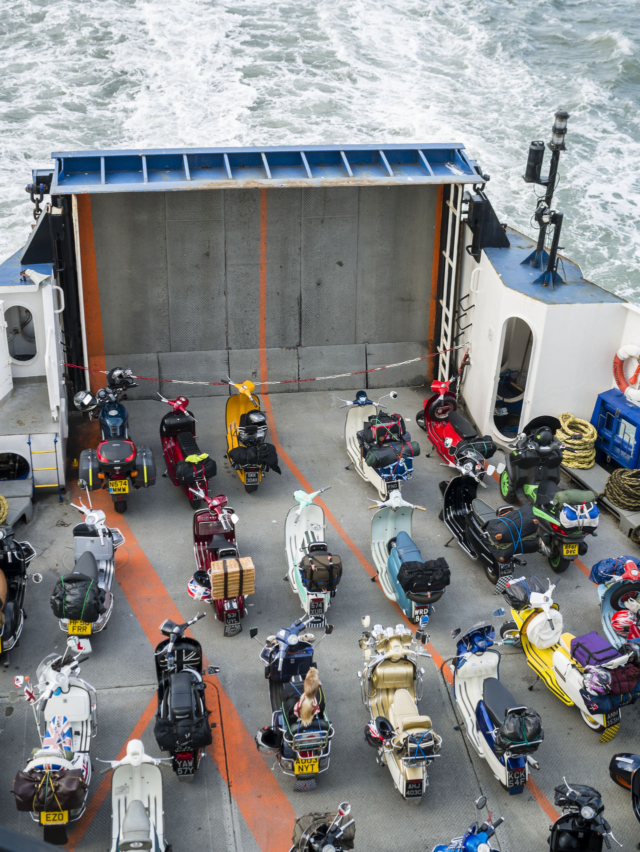 Scooters Lined up Onboard a Ferry, Portsmouth, Britain 1960's 60's Classic Crossing Custom Deck Ferry Ferryboat Italian Lambretta Lined Moped Motorbikes Parked Rally Retro Revival Scootering Scooters Sixties Transport Transportation Vehicle Vespa Vintage
